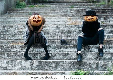 young halloween couple of two girls or women in black witch hat tights and jeans sitting on stony stairs with traditional autumn holiday symbol of orange spooky pumpkin and cap outdoor
