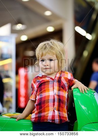 Cute baby boy blond child in plaid shirt drives green toy car in amusement park