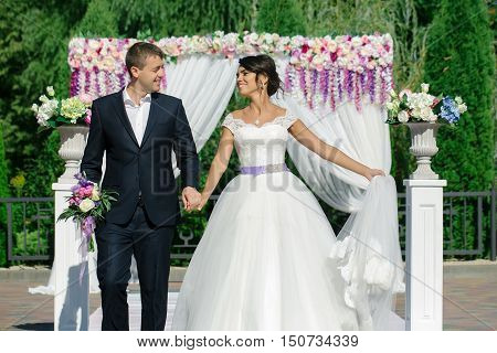 Beautiful bride and groom just married couple hold hands near arch decorated with flowers on wedding day on natural background