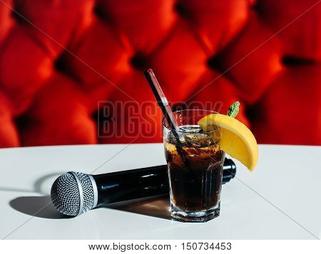 Black microphone and nonalcoholic cocktail with lemon and mint in glass with transparent and black rolls on white table on red background
