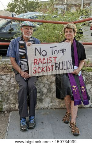 Asheville North Carolina USA: September 12 2016: Man and a woman wearing a Christian vestment hold protest sign at a Donald Trump campaign rally saying