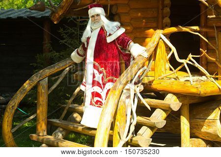 Santa Claus in red costume standing on stairs with beautiful handrails of wooden house outdoor