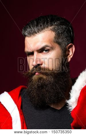 Handsome man hipster male with long beard and moustache in santa coat bends brows on purple background