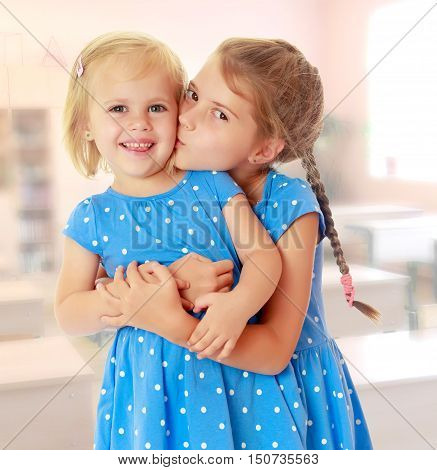 Two charming little girls, sisters , in identical blue dresses with polka dots. Older sister kissing the younger on the cheek.On the background of the school with desks
