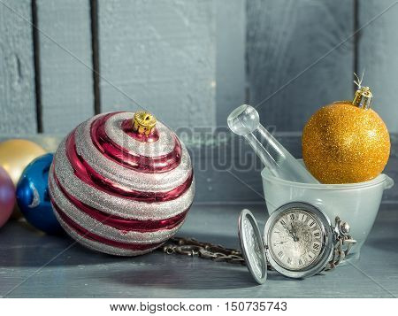 Silver clock on chain near white glass bowl and orange glitter christmas decorative balls on grey wooden background closeup