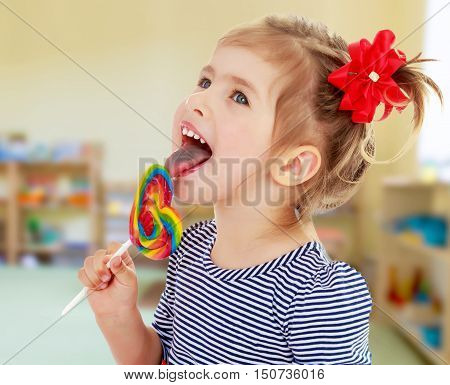 Cute little blonde girl with a red bow on her head, with pleasure licking colorful candy on a stick. Visible language which was painted in a candy color. Close-up. background of a child's room