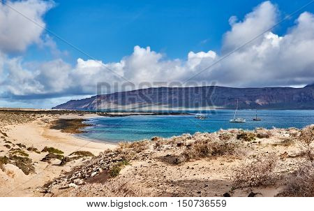 Beautiful seashore on Canary islands, paradise bay with untouched nature and a few ships. Seascape photographed on La Graciosa. Best for tourist attraction, design postcard or calendar.