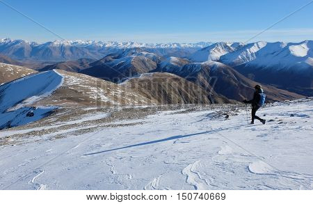 A Woman Hiker Strides Across Snowfield.  Castle Hill Peak, Southern Alps, New Zealand
