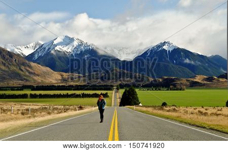 A Woman Walking the Long Road to Green Pastures and The Southern Alps.  Arthurs Pass, Canterbury, New Zealand