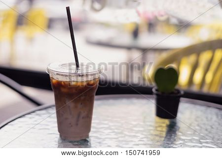 ice fresh coffee in see through plastic glass with small plant on table at coffee time
