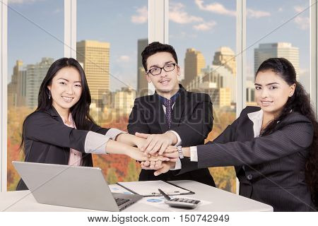 Image of a multi ethnic business people making pile of hands in the office while smiling and looking at the camera with autumn background on the window