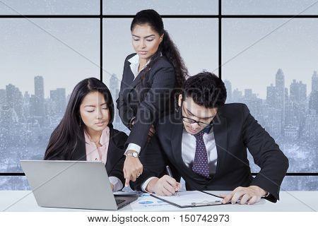 Portrait of leader showing mistake of report and two employee looking and writing new report with winter background on the window