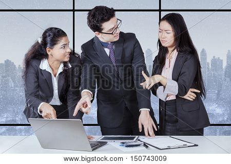 business people having conflict problem working in team together and they serious argument negative emotion at desk office with winter background on the window