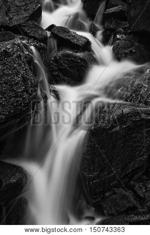 Beautiful Waterfall In Forest Landscape Long Exposure Flowing Through Trees And Over Rocks In Black