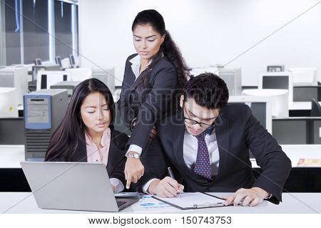 Two young employee working and sitting in the office while leader showing mistake of counting in the calculator with laptop and paperwork on the table