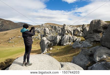 A Woman Hiker Photographs Giant Limestone Boulders.  Castle Hill Basin, Southern Alps, Canterbury, New Zealand