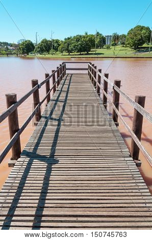 Deck made of wooden boards on lake water in a park with trees and green vegetation background on a sunny day. Rustic footbridge over water in perspective. Beautiful day in the park lake.