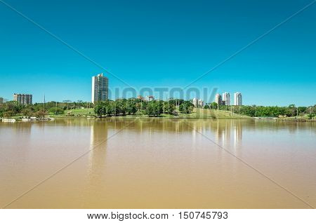 Park lake with vegetation, trees and some buildings in the background. Beautiful sunny day with reflection in water and a blue sky gradient. South America park, to relax with this beautiful view.