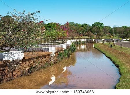 Stream of water between vegetation, some flowers and a blue sky in a park. Sunny day, reddish turbid water.