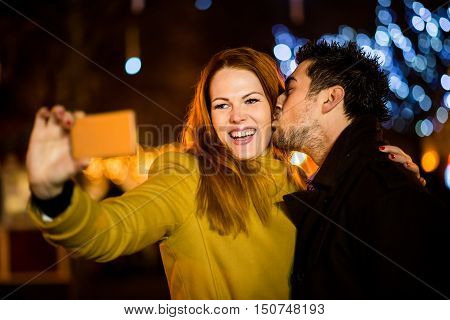 Young couple taking selfie by phone in christmas markets at night