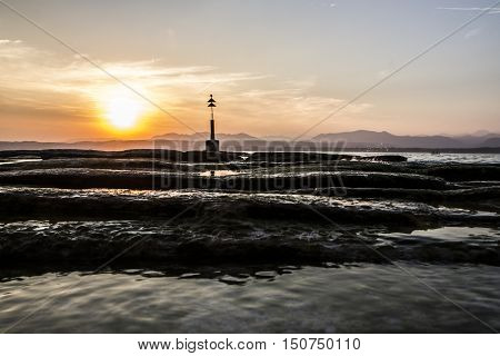 the lighthouse on the lake during a romantic sunset