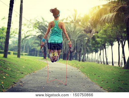 young fitness woman skipping rope at tropical park