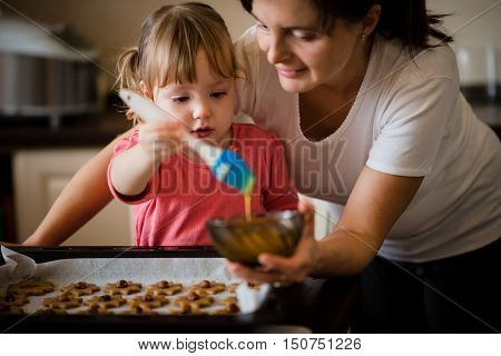Mother and child baking together - child spreading yolk on honey cakes