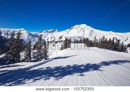 View to Alpine mountains surrounded by fog and ski slopes in Austria from Kitzbuehel ski resort with 54 cable cars 170 km prepared skiing slopes and place of famous hahnenkamm races.