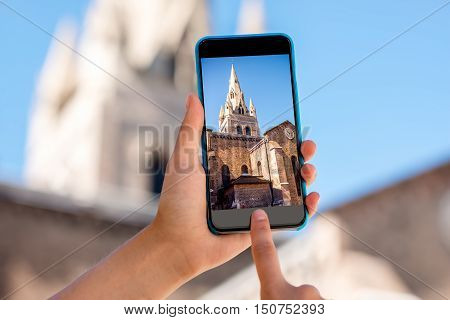 Holding a smart phone with photo of Saint Andrew church tower in Grenoble city in France