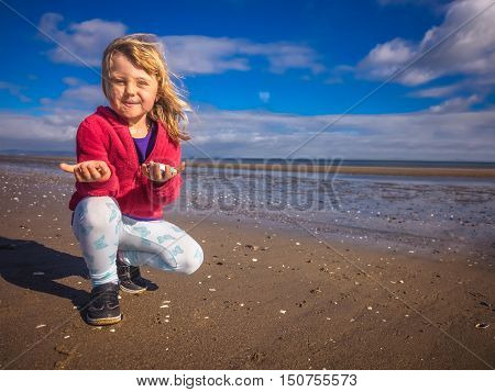 Young caucasian girl presenting small mussels found on the beach