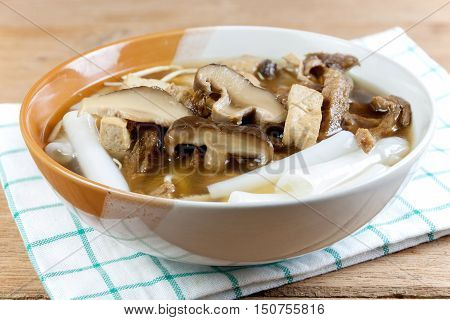 Vegetarian chinese roll noodle soup whit shiitake mushroom and tofu on wood table in Vegetarian festival