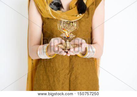 Fair Indian woman in traditional dress hands holding diya oil lamp and celebrating Diwali or deepavali, fesitval of lights.