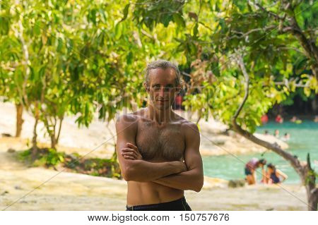 portrait of handsome topless man with crossed arms in front of a lake untr the trees