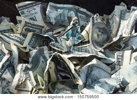 Pile of crumpled one hundred-dollar bills on the ground.