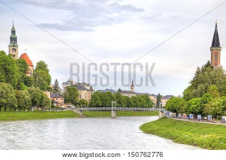 SALZBURG AUSTRIA - May 05.2012: City landscape. Salz River and the spiers of the Catholic Church on its banks