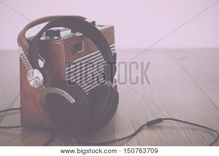 Headphones And Old Radio On Wooden Surface Vintage Retro Filter.