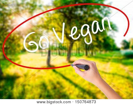 Woman Hand Writing Go Vegan With A Marker Over Transparent Board