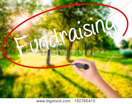 Woman Hand Writing Fundraising With A Marker Over Transparent Board