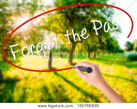 Woman Hand Writing Forget The Past With A Marker Over Transparent Board