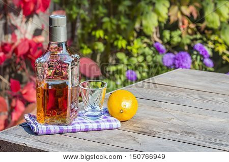 Bottle of tequila with a shot and the lemon on the old table in autumn garden's