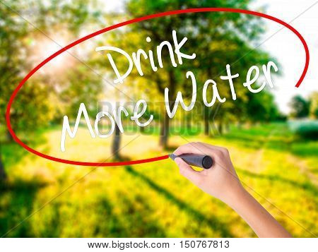 Woman Hand Writing Drink More Water With A Marker Over Transparent Board