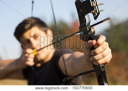 An archer drawing his compound bow in a field in the forest during the early autumn.