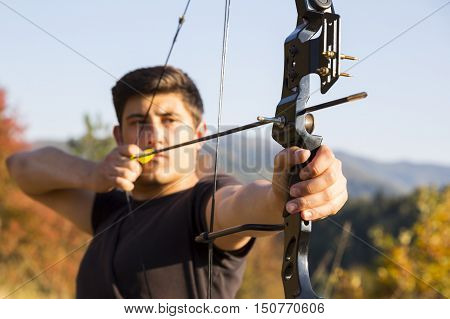 An archer drawing his compound bow in a field in the forest during the early autumn. Autumn trees in the background.