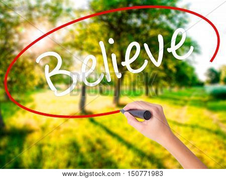 Woman Hand Writing Believe With A Marker Over Transparent Board