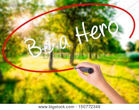 Woman Hand Writing Be A Hero  With A Marker Over Transparent Board