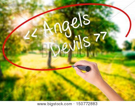 Woman Hand Writing Angels - Devils With A Marker Over Transparent Board .