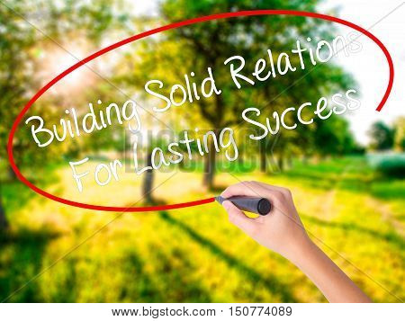 Woman Hand Writing Building Solid Relations For Lasting Success With A Marker Over Transparent Board