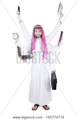 Multitasking concept. Arabian businessman standing in the studio with multitasking hands isolated on white background