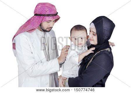 Male Arabian doctor using a stethoscope to check baby health with his mother isolated on white background