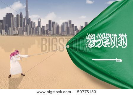 Picture of Arabian person wearing traditional clothes and pulling Arabian flag shot outdoors